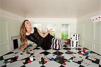 Young woman in small room throwing playing card Stock Photo - Premium Royalty-Freenull, Code: 614-03684573