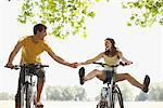 Happy couple riding bicycles and holding hands