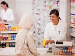 Pharmacist handing medication to customer in drug store