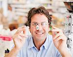 Customer trying in prescription eyeglasses in drug store Stock Photo - Premium Royalty-Free, Artist: Westend61, Code: 635-03685426