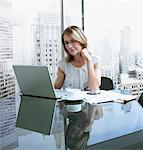 Woman working on computer with cityscape in background Stock Photo - Premium Royalty-Freenull, Code: 635-03685444