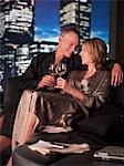 Couple in bathrobes drinking wine in living room at night Stock Photo - Premium Royalty-Free, Artist: Westend61, Code: 635-03685447