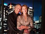 Couple in bathrobes hugging with city lights in background Stock Photo - Premium Royalty-Freenull, Code: 635-03685448