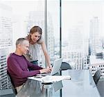 Couple working on computer with cityscape in background Stock Photo - Premium Royalty-Free, Artist: Blend Images, Code: 635-03685474