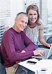 Couple working on computer with cityscape in background Stock Photo - Premium Royalty-Free, Artist: Blend Images, Code: 635-03685475
