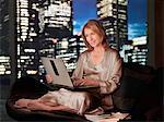 Woman in nightgown using laptop at night Stock Photo - Premium Royalty-Free, Artist: Ikon Images, Code: 635-03685492
