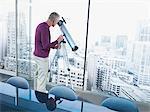 Man using telescope to look at city buildings Stock Photo - Premium Royalty-Free, Artist: Arcaid, Code: 635-03685493