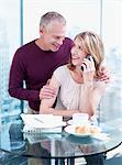 Husband hugging wife at breakfast as she uses cell phone Stock Photo - Premium Royalty-Free, Artist: Westend61                , Code: 635-03685580