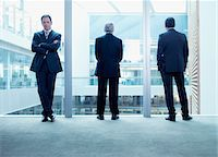 Businessmen standing near glass wall in office Stock Photo - Premium Royalty-Freenull, Code: 635-03685593