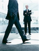 Businessman standing in corridor as co-worker rushes past Stock Photo - Premium Royalty-Freenull, Code: 635-03685616
