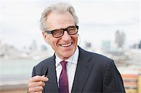 Smiling businessman using cell phone hands-free device Stock Photo - Premium Royalty-Freenull, Code: 635-03685621
