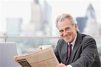 Businessman drinking coffee and reading newspaper Stock Photo - Premium Royalty-Freenull, Code: 635-03685654