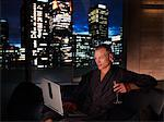Man in bathrobe drinking wine and using laptop Stock Photo - Premium Royalty-Free, Artist: Blend Images, Code: 635-03685679