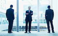 Businessmen standing near glass wall in office Stock Photo - Premium Royalty-Freenull, Code: 635-03685708