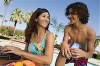 Mother and son (13-15) at swimming pool, mother using laptop. Stock Photo - Premium Royalty-Freenull, Code: 694-03692262