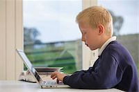 profile of school boy working on laptop at a desk Stock Photo - Premium Royalty-Freenull, Code: 621-03698723