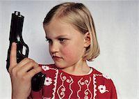 A young girl holding a gun Stock Photo - Premium Royalty-Freenull, Code: 653-03706739