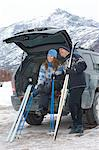 Couple relaxing at back of car, holding cross-country skis and poles in snow Stock Photo - Premium Royalty-Free, Artist: Scott Tysick, Code: 693-03707247