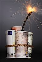 Rolls of money symbolizing dynamite with lit fuse, in studio Stock Photo - Premium Royalty-Freenull, Code: 693-03707697