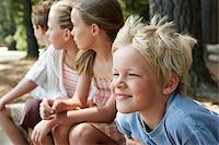 Four children (7-9) sitting in forest, close-up. Stock Photo - Premium Royalty-Freenull, Code: 693-03707822
