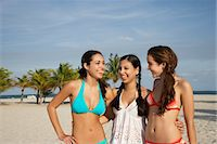 Three teenage girls (16-17) wearing bikinis, standing on beach, portrait Stock Photo - Premium Royalty-Freenull, Code: 693-03707944