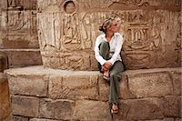 egyptian hieroglyphics - Egypt, Karnak. A tourist sits at the base of a massive stone column in the Great Hypostyle Hall. Stock Photo - Premium Rights-Managednull, Code: 862-03710911