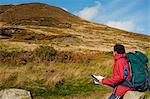 Wales, Clwyd.  A trekker stops to read his map as he approaches Moel Arthur in the Clywydian Hills. Stock Photo - Premium Rights-Managed, Artist: AWL Images, Code: 862-03714253