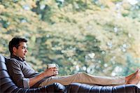 Man reclining in chair drinking coffee Stock Photo - Premium Royalty-Freenull, Code: 635-03716154