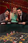 Excited friends winning at craps table Stock Photo - Premium Royalty-Free, Artist: Westend61, Code: 635-03716336