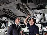Businessman looking underneath car with mechanic Stock Photo - Premium Royalty-Freenull, Code: 635-03716382