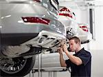 Mechanic working on car in auto repair shop Stock Photo - Premium Royalty-Free, Artist: Blend Images, Code: 635-03716397