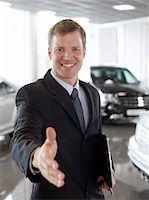 Greeting salesman in automobile showroom Stock Photo - Premium Royalty-Freenull, Code: 635-03716400