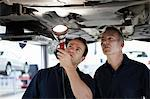 Mechanics looking underneath car in auto repair shop Stock Photo - Premium Royalty-Freenull, Code: 635-03716401