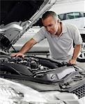 Mechanic repairing car engine Stock Photo - Premium Royalty-Free, Artist: Blend Images, Code: 635-03716402