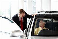 Salesman talking to man in new car in showroom Stock Photo - Premium Royalty-Freenull, Code: 635-03716412