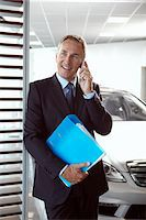Salesman holding binder and talking on cell phone in automobile showroom Stock Photo - Premium Royalty-Freenull, Code: 635-03716414