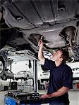 Mechanic working underneath car Stock Photo - Premium Royalty-Free, Artist: Blend Images, Code: 635-03716415