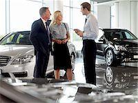 Salesman talking to couple in automobile showroom Stock Photo - Premium Royalty-Freenull, Code: 635-03716423