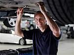 Mechanic working underneath car Stock Photo - Premium Royalty-Free, Artist: Blend Images, Code: 635-03716440