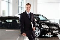 Salesman leaning on new car in showroom Stock Photo - Premium Royalty-Freenull, Code: 635-03716454