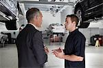 Businessman talking to mechanic in auto repair shop Stock Photo - Premium Royalty-Free, Artist: Blend Images, Code: 635-03716459