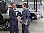 Businessman shaking hands with mechanic in auto repair shop Stock Photo - Premium Royalty-Free, Artist: Blend Images, Code: 635-03716478