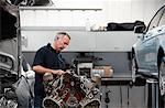 Mechanic working on engine in auto repair shop Stock Photo - Premium Royalty-Free, Artist: Blend Images, Code: 635-03716479