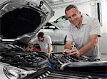Mechanic working on engine in auto repair shop Stock Photo - Premium Royalty-Free, Artist: Blend Images, Code: 635-03716481