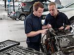 Mechanics working on engine in auto repair shop Stock Photo - Premium Royalty-Free, Artist: Blend Images             , Code: 635-03716492
