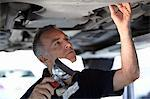 Mechanic working underneath car Stock Photo - Premium Royalty-Free, Artist: Blend Images, Code: 635-03716497
