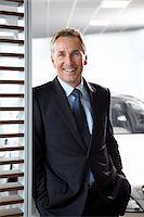 Salesman standing in automobile showroom Stock Photo - Premium Royalty-Freenull, Code: 635-03716504