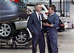 Businessman talking to mechanic in auto repair shop Stock Photo - Premium Royalty-Free, Artist: Blend Images, Code: 635-03716505