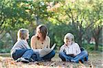 Mother Reading with Sons Outdoors