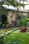 Suburban Garden. Checkerboard paving stone and grass, agapanthus in large terracotta pot, conservatory and sail shade. Stock Photo - Premium Rights-Managed, Artist: Arcaid, Code: 845-03720928
